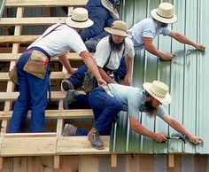 At an Amish barn raising, a helping hand holds a brother from falling off edge , while he nails metal roof to barn rafters.