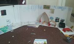 Cardboard box made into zoo and  house using pens and cardboard