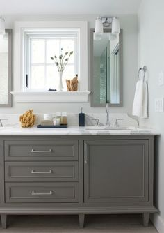 Small bathroom with gray vanity and cabinet.