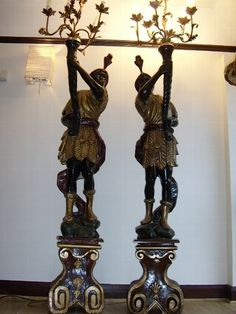 A fine pair of softwood antique Venetian Blackamoor Torcheres with metal sculptured Candlearbra and decorated with leaves.