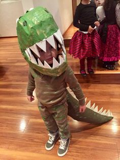 Kids Costumes. DIY Dinosaur T-Rex costume. A dino tail, a dino head made of paper mache and worn over a cycling helmet. Not easy but quite adorable.