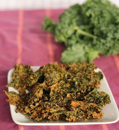 Cheesy Yet Vegan Kale Chips  3/4 cup cashews 1 bunch kale, washed and dried 1/2 red bell pepper, stem and seeds removed, chopped into large pieces 1 clove garlic, peeled 1 tablespoon soy sauce 2 tablespoons vegetable oil 1/3 cup nutritional yeast (not to be confused with Brewer's yeast) 1 lemon, peeled, cut into wedges, and de-seeded as much as possible (a few stragglers are ok)