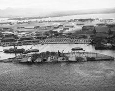 The battleship USS Oklahoma, capsized in the Pearl Harbor Attack on 7 Dec 1941, is righted to about 30-degrees during her salvage work, 29 Mar 1943.  Source   United States Navy Identification Code   80-G-410533