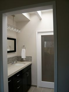 After: view of dressing area from bedroom showing pocket door with frosted glass so skylight light passes through into a bathroom with no windows.