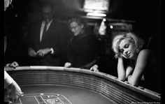 Marilyn at the Craps table of the Christmas Tree casino in Reno. Husband Arthur Miller in the background.