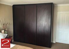 Bedroom cupboard sliding doors in Burgundy Mahogany finish with matt black powder coated handle profiles.