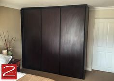 Bedroom cupboard sliding doors in Burgundy Mahogany finish with matt black powder coated handle profiles.