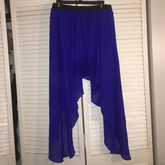 High low skirt This skirt is long on both sides and short in the front and back. An electric blue with a black elastic band at the waist Skirts High Low