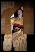 Maiko girl - Geisha apprentice - behind the curtain of a teahouse, Kyoto, Japan