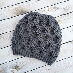 This is a PDF crochet pattern for a wonderfully chunky and uniquely-textured slouch worked from the bottom up. Even though it's solid, the texture of the cables reminded me of a chain link fence. It's a fun one to m