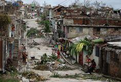 People walk on a street littered with debris after Hurricane Sandy hit Santiago de Cuba, on October 26, 2012.