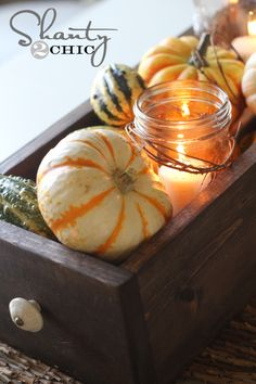 Fall table centerpiece.  A couple pieces of wood, mini gourds and mason jars/candle holders are all you need to make this fantastic Fall centerpiece!