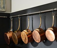 Chrome or stainless steel rails installed on a back splash become a stylish storage system for pots and pans as well as kitchen utensils. Hooks suspend necessities from the rail, making it easy to find what you need or put it away.