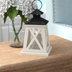 """Everything looks better in the candlelight! With its coastal lighthouse looks and rustic appearance, this vintage-inspired wooden lantern is the perfect vessel for your favorite candles. Crafted from iron and wood, white """"X"""" trim highlights the clear glass panels of this four-sided lantern, while its black roof features a hanging loop for a functional look. Wind-swept and weathered for antique charm, this piece is designed to accommodate tealights and other small candles."""