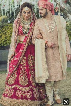 Luxurious Bridel Groom Dress In Red Lahnga Choli And Pinkish Sherwani.Bridal Lahnga Choli With Pure Dabka,Zari,Nagh,And, Threads Work.Groom Sherwani Based On Pure Jamawar Fabric In Light Pinkish Color.