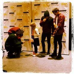 Harry taking a picture of a little girl's 1D shoes lol