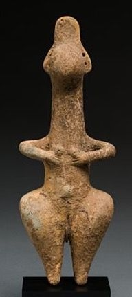 "Amiash Idol, Ancient Near East. 1st millennium BCE. Terracotta. Amlash refers to sites in the province of Gilan, Iran, along the Caspian Sea. Figures and animals were made in ceramic and bronze. The figures with ""button"" faces are thought to have been used in conjunction with burial rituals."