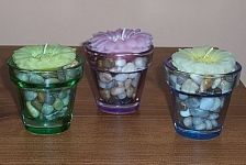 Fill small votive candle holders with mini river rocks and top with floating candles.