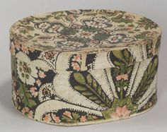 "Skinner says: ""Oval Wallpaper Covered Storage Box, Massachusetts, c. 1840, the box covered in a floral pattern in shades of green, salmon, black, and white, the interior lined with Boston area newspapers, with 1840 the latest date noted, (minor wear), ht.4 5/8, dia. 9 1/8 in."""