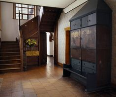 Interiors. Stair hall, Red House, 1859-1860; Bexleyheath, Kent, England; Philip waebb. The Entrance Hall at Red House with a cupboard painted by William Morris and the oak staircase with its vertical tapered newel posts.