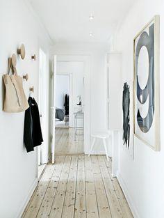 Door een rustige lichte basis in de gang krijgen je spullen alle aandacht. Meer dan een kapstok en spiegel heb je niet nodig in een minimalistische hal.