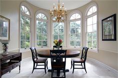A rotunda breakfast room with protruding wall of windows - too formal and empty for my personal style, but I like the windows, although not the curved portions at the top. That almost comes off poorly planned. Drapery would be a nightmare with those tops.