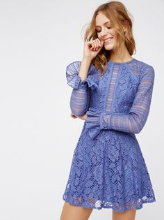 Kiss And Tell Lace Mini | Long sleeve lace mini dress featuring a femme fit-and-flare shape. Small button closures at the back keyhole cutout and at the ruffled and flared sleeve cuffs. Hidden side zipper closure. Partially lined.