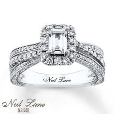 Round diamonds beautifully frame the emerald-cut center in this stunning engagement ring from Neil Lane Bridal.