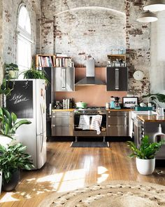 Wow! This is such a beautiful kitchen! I love everything about it, from the exposed walls to the plethora of gorgeous plants, the flooring and appliances!