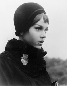 A young Jane Fonda accessorises a plain black scarf with an oversized brooch.