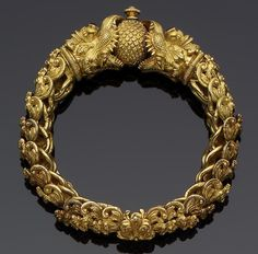 India ~ Tamil Nadi | Gemset gold bracelet; interlinking elements in the form of floral kirttimukhas, the termimals in the form of makara heads, holding an orb between their open mouths, the eyes gem-set. From the 1st half of the 20th century
