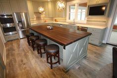 Remodelling Transitional Kitchen with Dark Walnut Island Butcher Block Countertop, Rattan Round Wave Pendant Ceiling Light, and Built in Television Kitchen Cabinets