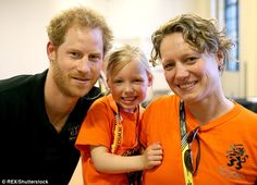 Prince Harry is pictured with a Dutch competitor and her daughter at the Invictus Games in...