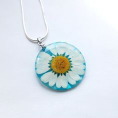 Pressed English Daisy Necklace Resin Pendant Real Flower Blue Transparent Pendant 925 Silver Plated. $28.00, via Etsy.