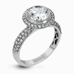 This classically-styled white gold engagement ring features a circular halo and is highlighted by .43 ctw of sparkling round cut white diamonds.