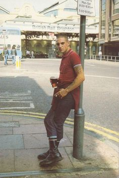 A Skinhead leans against a post in Brighton by the station entrance.