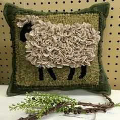 Primitive rug hooked with proddy sheep pillow. It is backed with green plaid wool. The edges are hand whipped wool yarn. Designed by Kris Miller of Spruce Ridge Studios. Offered for sale by Kountry Road Prims & Such in Shelbyville, TN. Contact them via their Facebook page.