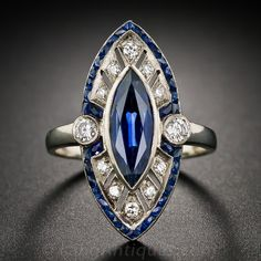 A slender, streamlined and stunning navette shape dinner ring starring an elegantly modeled marquise sapphire weighing 2.00 carats. The enchanting royal blue gemstone is set in a full bezel atop a sparkling frame of diamonds which, in turn, is outlined by tiny French-cut calibre sapphires. For a finishing touch, a pair of round diamonds glitter on each side above the ring shank