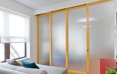 Custom sliding wall partition with painted solid wood frames, frosted acrylic and ecoresin panels, and a top-hung/multiple bypass track system