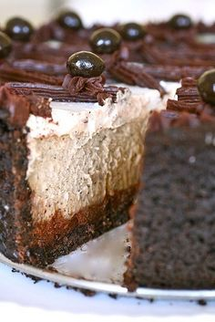 cappuccino fudge cheesecake, The base is a chocolate cookie crumb crust with a layer of ganache on the bottom.  The filling is a rich, smooth coffee-flavored cheesecake and the topping is a thin layer of sweetened vanilla sour cream. Garnished with more ganache and chocolate-covered espresso beans