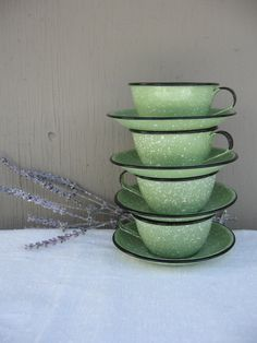 Mint Green Enamel Teacups and Saucers - Vintage Green Graniteware - Enamelware - French Country Decor    Pretty set of four mint green graniteware teacups and saucers. Teacups and saucers are metal overlaid with mint green enamel with white splatters and black trim. Perfect for a shabby French Country kitchen. Listing is for four cups and four saucers--eight pieces in total.    *Condition: Very Good. Teacups and saucers are in Very Good condition. Enamel is in very good condition on cups and…