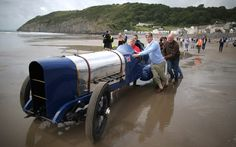 Don Wales (in blue top) pushes the original Sunbeam car onto the beach as he recreates his grandfather's 1925 land speed world record at Pendine Sands in Carmarthen, Wales. Sir Malcolm Campbell drove his 350hp Sunbeam on July 21, 1925 on the sands to reach a new world record of 150.76 miles per hour. The car was bought in 1957 and restored by Lord Montague for his National Motor Museum at Beaulieu in Hampshire.