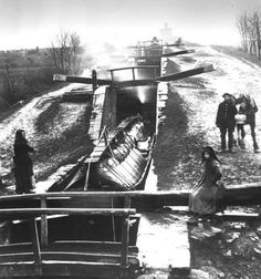 Lock gates and narrow boat in winter, with three boat people and their horse © Foxton Canal Museum