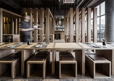 Slatted timber boxes contain dining areas inside this noodle bar in Shenzhen.