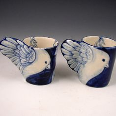 This is a pair of small hand formed and hand painted cups with bird wings as handles and ladies on the front of each. One is 2.6 tall and the other