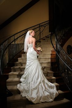 This picture was captured by Trystan Photography at one of Mark Christopher Weddings & Events' weddings at Cielo at Castle Pines. The romantic, soft feel of the bride's dress is dramatically captured as it cascades down the venue's stairs into the main room. We also love that this photo was taken in the middle of the day, but appears to be in a room that is only lit by candles!