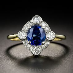 Recently crafted in Great Britain in emulation of classic early-twentieth century Edwardian style, a gorgeous royal blue cushion-cut sapphire, weighing 1.04 carats, radiates from within a lovely and lively lozenge-shape frame rendered in platinum over 18K gold, and sparkling all around with bright white diamonds accentuated with delicate milgraining. 1/2 inch, currently ring size 6 1/2.
