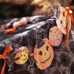 Search the Internet for free vintage Halloween clip art. Print your favorite images on cardstock, cut out, punch a hole on each side, and string together with orange ribbon. Hang the garland on your fireplace mantel, inside a window, or along the edge of a table as shown here.