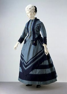 Boating Dress | c. 1872   Almost bustle era  This is a jaunty, sensible woman's outfit of the early 1870s designed for boating or seaside walking. A hemline just at the ankle indicates a garment intended for walking outdoors. The style of the dress has been inspired by the colors and stripes of sailors' uniforms. Made of cotton, easily washed and dried. Despite its practical use, the ensemble still incorporates the details of fashionable dress, with an overskirt in front & a bustle worn…