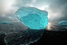 氷山美術館 >【Traveler Photo Contest 2014 - National Geographic】> 別の時代に居るみたいな、それか、全く違う星にいるような、そんな風景。アイスランドのバトナヨークルトル氷河の河口を通ってヨークルサルロン氷河湖を下った。氷山はここで北極海に流れ込み、海によって磨かれる。そして潮によって再びアイスランドの黒い砂浜の上に押し戻される。さながら、まるで巨大な氷山の美術館のようだ。この写真は嵐のあと、夕方に撮ったものだ。氷山の大きさはジープぐらいである。(写真と文章:サム・モリス)
